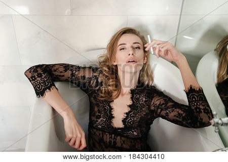 Young confident woman with cigarette lying in bath