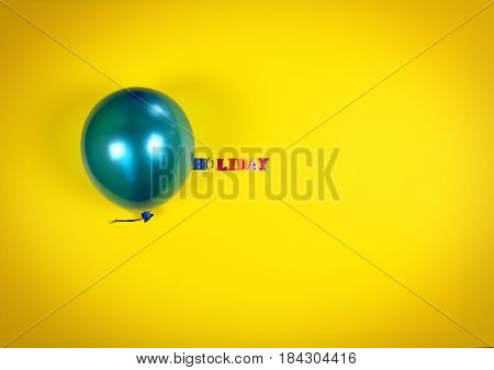 Blue balloon and inscription holiday on a yellow surface empty space on the right