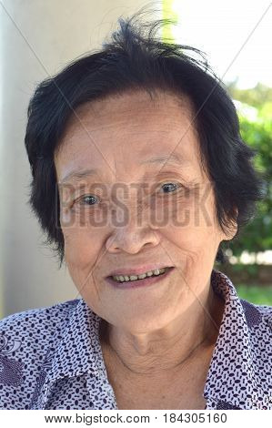 An elderly asian woman smiling at the camera