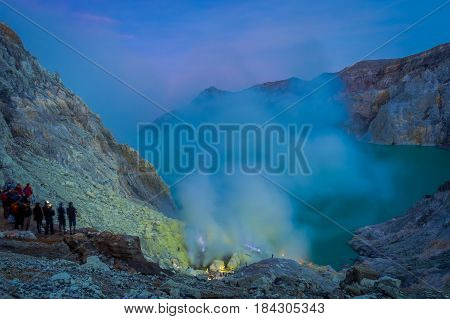 KAWEH IJEN, INDONESIA: Nice overview of sulfur mine with miners working next to volcanic crater lake, spectacular nature.