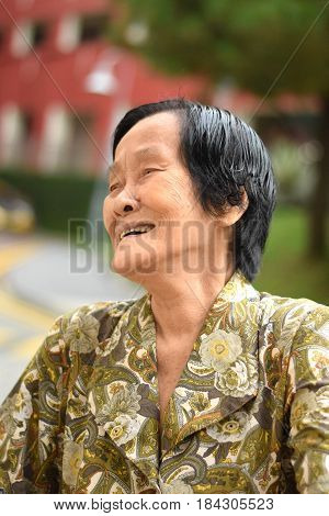 An elderly asian woman laughing happily outdoor