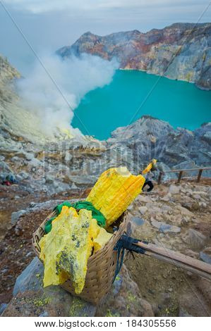 KAWEH IJEN, INDONESIA: Yellow sulfur rocks inside baskets, spectacular volcanic crater lake background, tourist hiking attraction.