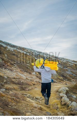 KAWEH IJEN, INDONESIA: Local miner carrying heavy load of yellow sulfur rocks up mountain side, tourist hiking attraction located inside volcanic crater, spectacular nature.