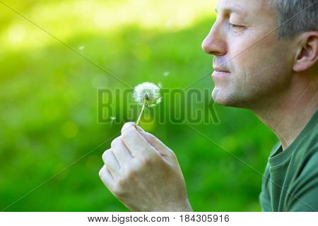 Man with dandelion over blurred green grass, summer nature outdoor