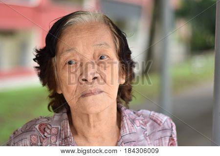 A sad looking asian woman posing outdoor