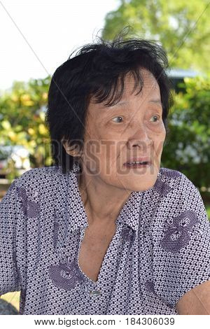 An elderly asian woman looking sideway outdoor