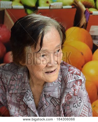 An elderly asian woman posing in front of a poster of fruits