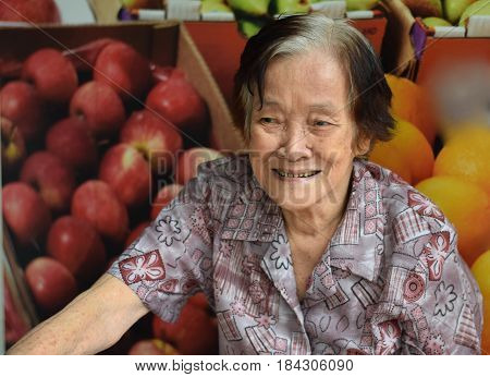 An elderly asian woman laughing happily in front of a poster of fruits