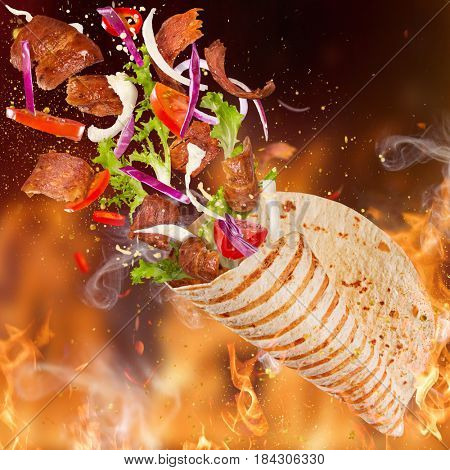 Close-up of kebab sandwich with flying ingredients with fire flames background.
