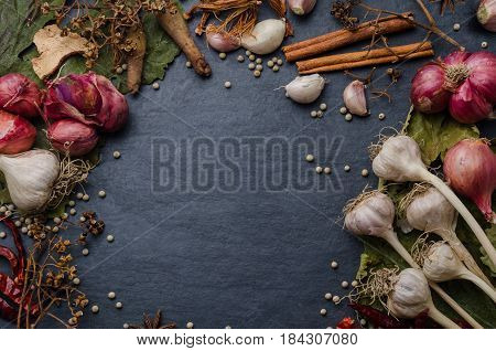 Various spicy ingredients with dried herbs on black stone background