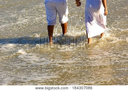 Couple wetting their feet in romantic walk barefoot at the edge of the sea