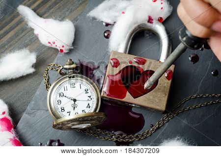Hand holding a screwdriver with red heart shape over padlock blood and vintage pocket watch on black stone background