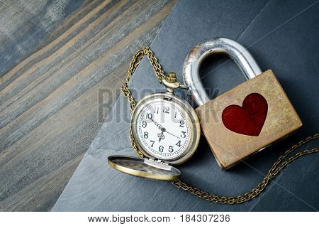 Red heart shape over padlock with vintage pocket watch on black stone background