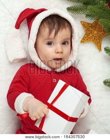 baby portrait in christmas decoration, dressed as Santa, lie on fur near fir tree and play with gifts, winter holiday concept