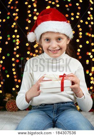 child girl portrait in christmas decoration, dressed in Santa hat, boke lights on dark background, winter holiday concept