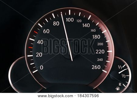 Speedometer of a car showing 90, glowing red