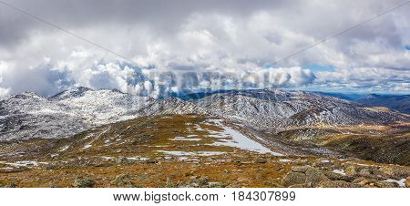 Snow Covered Peaks And Yellow Grass Under Clouds. Australian Alps Panoramic Landscape