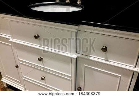 Interior design of a contemporary white bathroom cabinet and elegant dark granite counter top, porcelain sink and chrome knobs. Wooden cabinetry white bathroom style