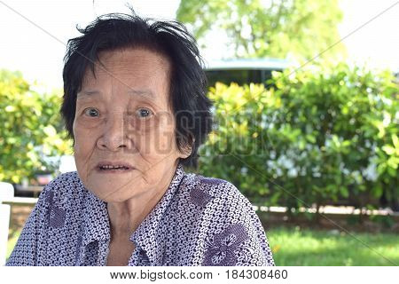 A sad looking elderly asian woman looking at camera