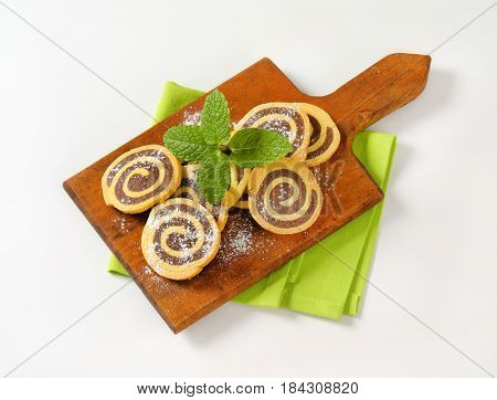 sweet chocolate rolls on wooden cutting board