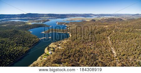 Aerial Panorama Of Snowy River Flowing Among Green Hills Of Australian Alps And Lake Jindabyne