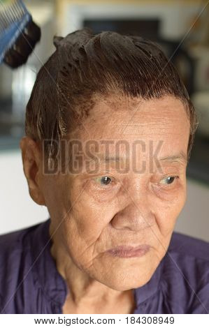 An asian elderly woman doing some colouring to her hair
