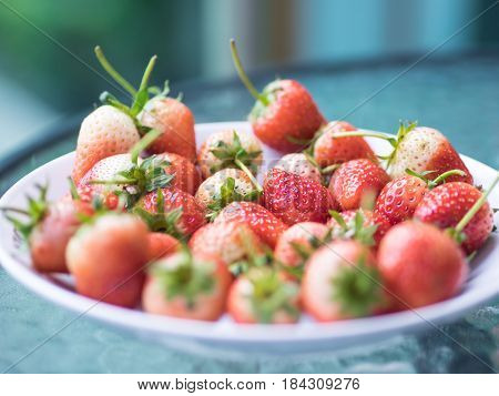 Fresh ripe natural strawberry red and white fruit on glass table