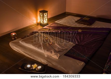 Empty dark room with mats for thai massage and lamps on floor