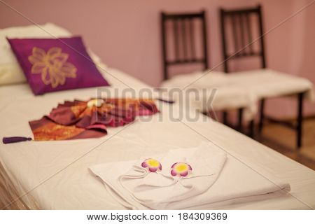Lounge for thai massage with towel, pillows and flowers in empty room with chairs