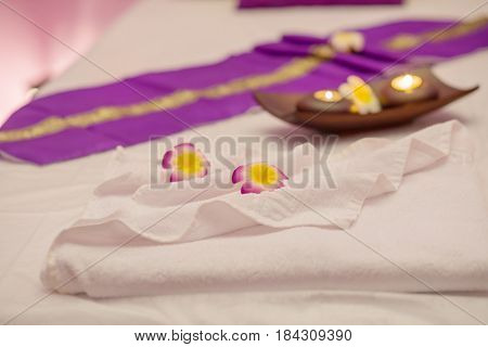 Asian sash, flowers on white towel, candlesticks with candles on couch, focus on flowers