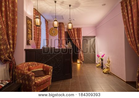 Wooden reception with carving in thai day spa with asian decoration