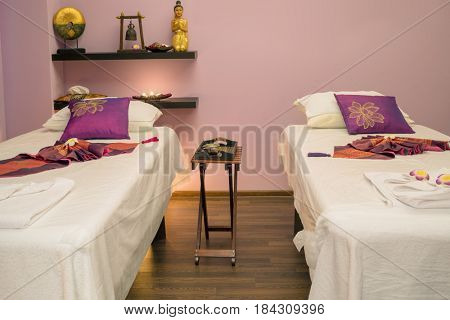 Lounges for thai massage with towels and flowers in empty room