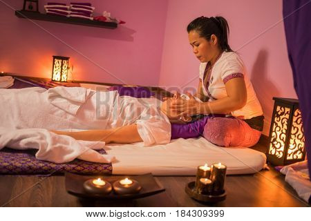Asian woman does thai massage for woman on mat in private spa room