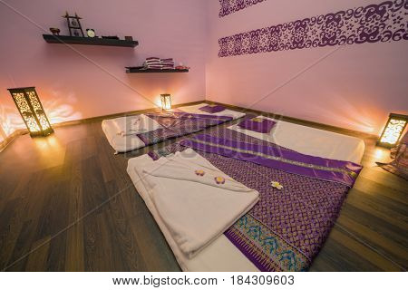 Empty pink cozy room with mats for thai massage and lamps on floor