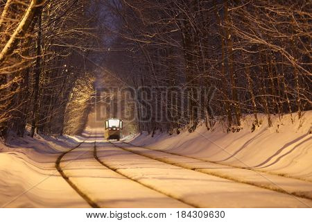 Tram moves on railway on road in park at winter snowy evening, back view
