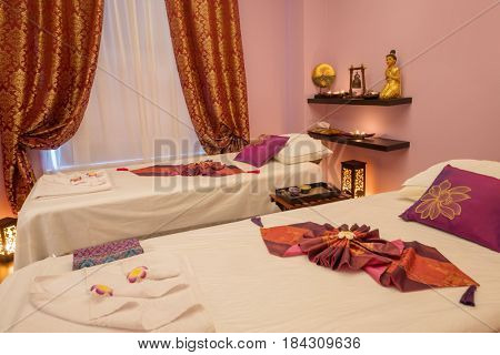 Empty pink cozy room with two beds for thai massage and asian decoration