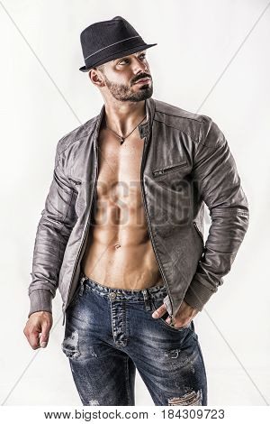 Confident, attractive muscleman with open jacket on muscular torso, ripped abs and pecs, wearing fedora hat, with hand in a pocket