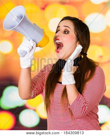 Closeup portrait of female clown mime screaming with a megaphone over a colorful background