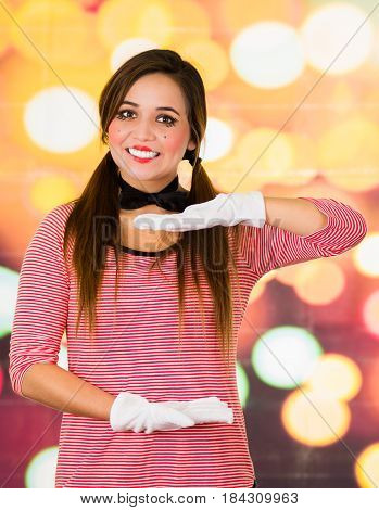 Closeup portrait of happy female clown mime posing with hands holding empty space