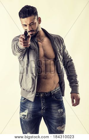 Handsome man wearing leather jacket on naked muscular torso pointing gun to camera, on light background, looking straight aiming