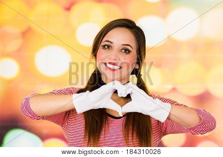 Closeup portrait of female clown mime making a heart with hands, concept of love