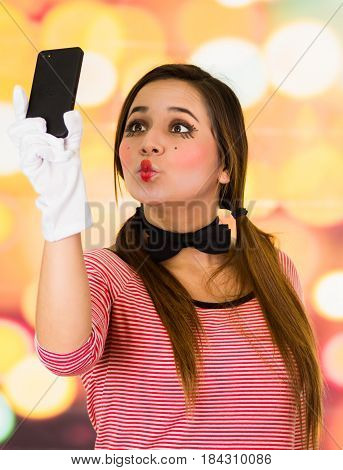 Closeup portrait of cute young girl clown mime taking selfie with cell phone sending a kiss