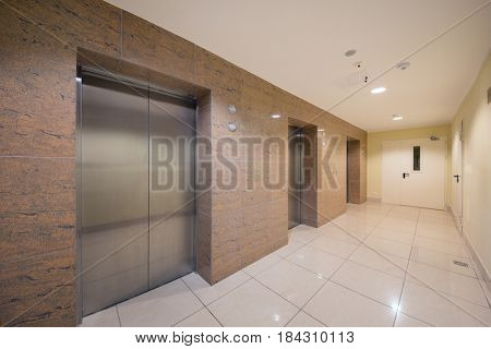 Empty white hall with metal elevator doors in modern building