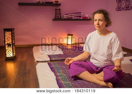 Woman meditates on mat in purple spa room for thai massage