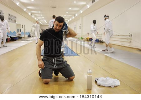 Man wipes sweat by towel in gym for fencing training, other people out of focus