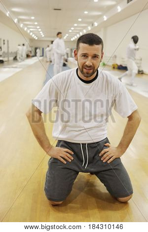 Man sits in floor in gym for fencing training, other people out of focus