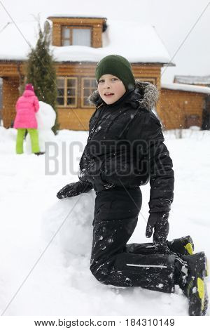 Boy sculpts snowman near wooden country house during snowfall at winter day, girl out of focus
