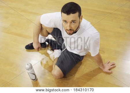Handsome man sits on floor with bottle of sport cocktail in gym after training
