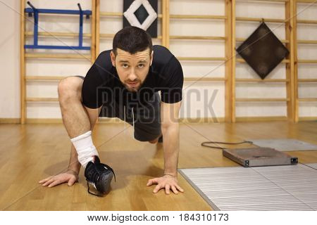 Handsome man in black does stretching on floor in gym after training
