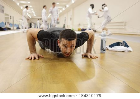 Man press-up in gym for fencing training, other people out of focus